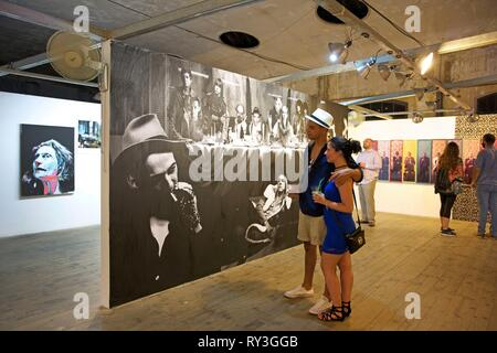 Cuba, La Havana, Vedado, young couple in front of a contemporary work of Maurice Renoma exposed in the industrial setting of the multicultural center La Fabrica de arte cubano - Stock Image
