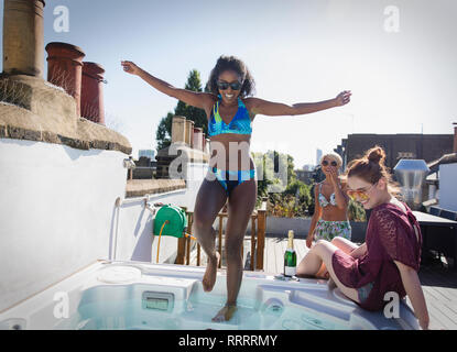 Carefree young women friends in bikinis at rooftop hot tub - Stock Image