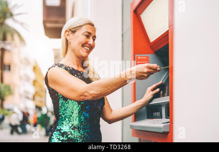 Happy mature woman withdraw money from bank cash machine with debit card - Senior female doing payment with credit card in ATM - Stock Image
