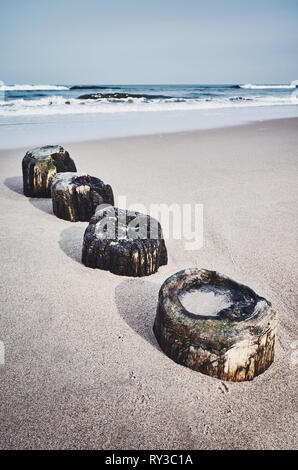Old wooden sea breakwater remains on a beach, selective focus, color toning applied. - Stock Image