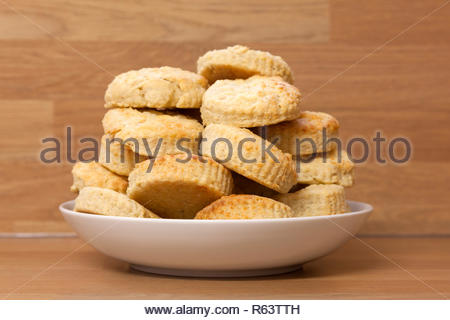 Home baked cheese scones stacked on a plate - Stock Image
