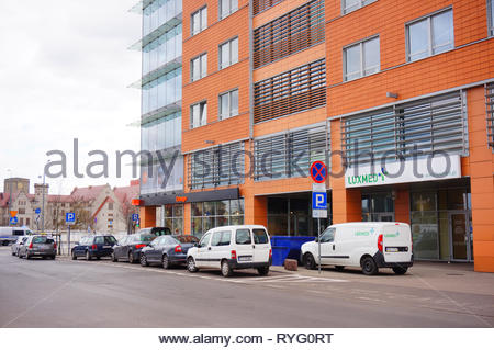 Poznan, Poland - March 8, 2019: Row of cars parked in front of a Luxmed medical office and a Orange salon in the Globis building on the Slowackiego st - Stock Image