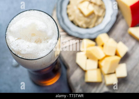 Delicious mix, dark Belgian beer and pieces of hard cheese with mustard close up - Stock Image