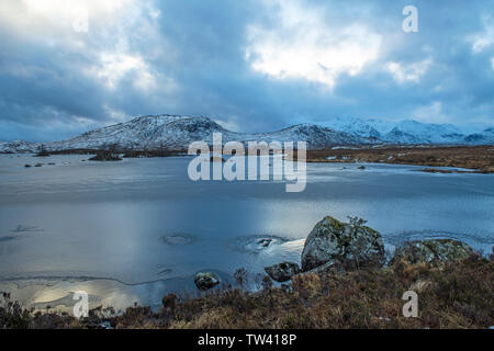 Rannoch Moor and Lochan in Scotland near Glen Etive and Glencoe in winter with snow on the ground and ice across the lochan. - Stock Image