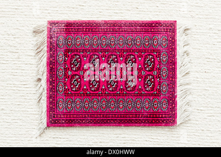 A red asian rug on a white cloth surface - Stock Image