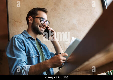 Photo of laughing caucasian man wearing glasses reading documents and talking on cellphone while working in cafe indoors - Stock Image