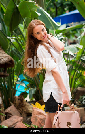 single young lady in her 20s indoor and outdoor portraits taken in autumn in London. Beautiful and attractive smile. - Stock Image