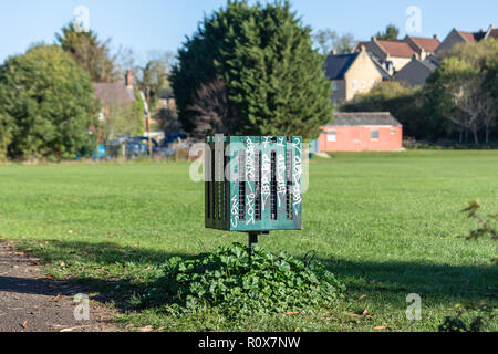 Graffitied green colour public litter bin, square in shape with slatted sides and cage interior on the edge of an open playing field in Chippenham UK - Stock Image