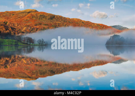 Cloud pressure inversion on a cold autumnal morning over Grasmere Lake & River Rothay, below the summits of - Stock Image
