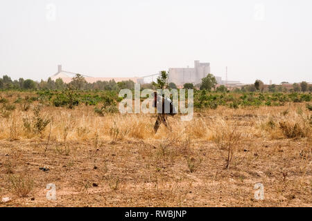 Business and security in Africa: A US paratrooper walks past a cement factory near Bobo-Dioulasso in Burkina Faso, west Africa, during training - Stock Image