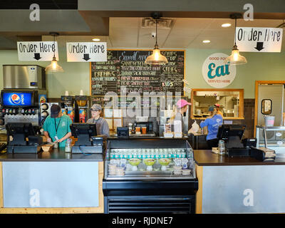 Deli cafe or restaurant front order counter with female employees working behind the counter at Sweet Creek Farm Market in Pike Road Alabama, USA. - Stock Image