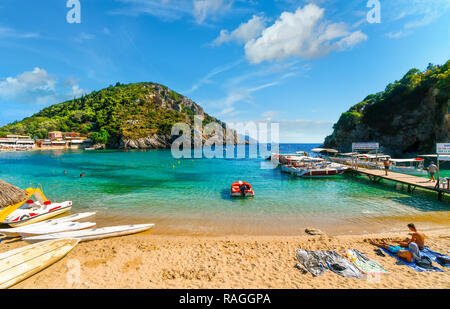Tourists relax in the clear waters and on the sandy Palaiokastritsa beach and bay near the boat dock on the Aegean island of Corfu, Greece. - Stock Image