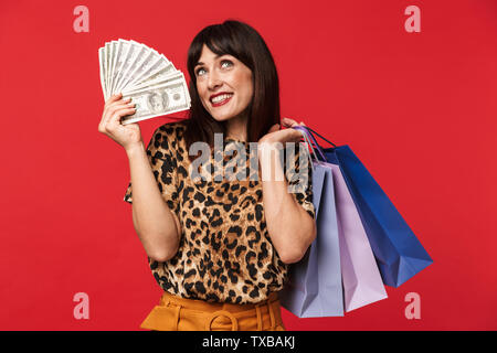 Image of a beautiful happy young woman dressed in animal printed shirt posing isolated over red background holding money and shopping bags. - Stock Image