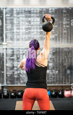 Rear view of a muscular young woman swinging a kettlebell weight and holding it above her head with one hand during training inside a gym - Stock Image