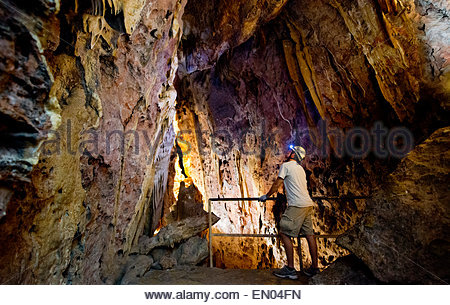Inside the Fault Room in Colossal Cave, Tucson, Arizona. A cave guide looking toward the fractured limestone walls. - Stock Image