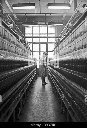 This weaver of the Tryokhgornaya Manufaktura factory is a member of a Communist labor team and operates five rather - Stock Image