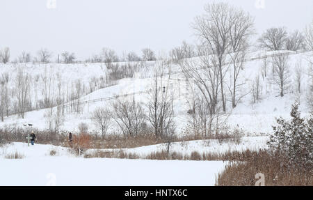 People and dogs on hiking trail in snow. - Stock Image
