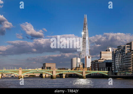 The London Shard with sunburst and light reflection in River Thames, South Bank with Southwark Bridge and London Bridge behind Southwark London UK - Stock Image