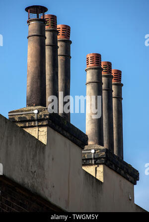 tall Louvred Chimney pots six chimney pots on rectagle stack. - Stock Image