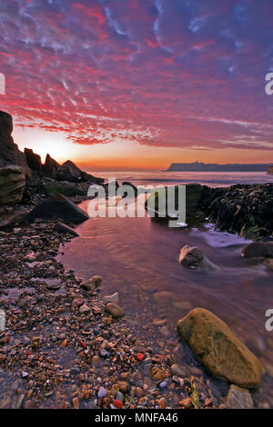 Sunrise in Scarborough's North Bay, where Scalby Beck flows into the sea under dawn-pink clouds - Stock Image