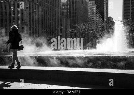 Woman walking alongside fountain in New York City - Stock Image