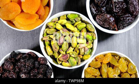 Selection of Healthy Fruit and Nut Snacks in White Bowls Looking Down, pistachio nuts, sultanas, raisins, soft apricots and prunes. - Stock Image