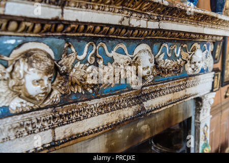 Smoke stained ceramic tiles of a hearth around a very old fireplace in a stately home. - Stock Image