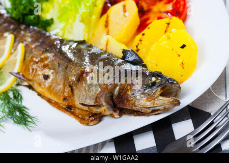 Fried trout fish served with baked potatoes, tomatoes and fresh greens - Stock Image