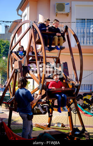 Young children enjoying on a traditional man driven small ferris wheel at a Spanish village Fiesta. - Stock Image