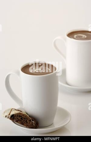 White porcelain cups with drinking chocolate. Almond and chocolate biscoti in saucer. Studio shot.      Ref: CRB538_103609_0010  COMPULSORY CREDIT: Ma - Stock Image