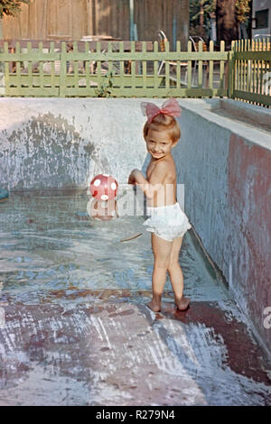 young girl plays in small garden swimming pool 1950s hungary - Stock Image