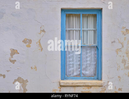 Minimalist capture of a single rural window on a white textured wall with peeling paint.  Simple window with blue farme, and white curtains - Stock Image