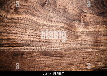 Walnut wooden cutting board with vignette shot from above in flat lay position. - Stock Image