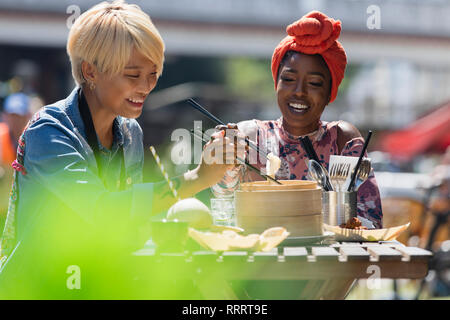 Young women friends enjoying dim sum lunch with chopsticks at sunny sidewalk cafe - Stock Image
