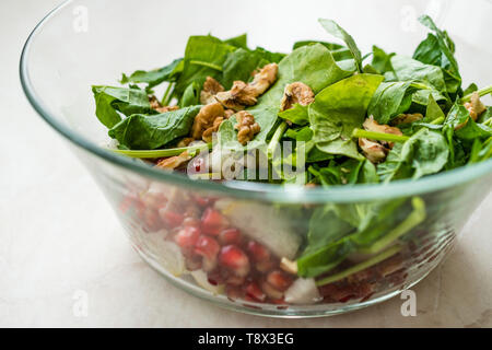 Fresh Walnut Salad with Pomegranate and Pear Slices in Glass Bowl. Ready to Make. Organic Food. - Stock Image