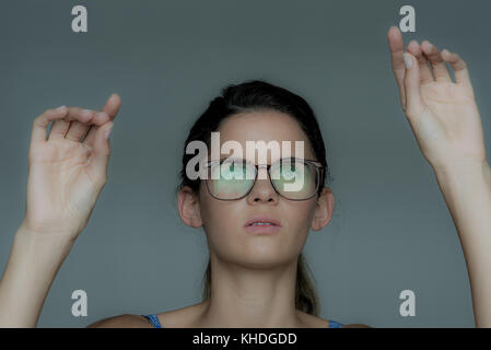 Young woman gesturing as if using touch screen technology - Stock Image