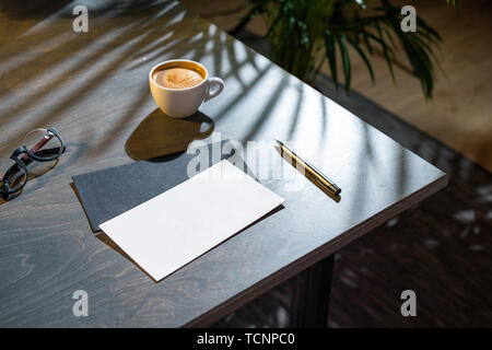 Close up of white coffee cup, blank envelopes and glasses and pen on dark wooden table with tropic plant on background. - Stock Image