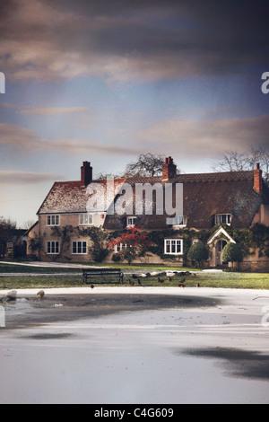 frozen pond in village - Stock Image