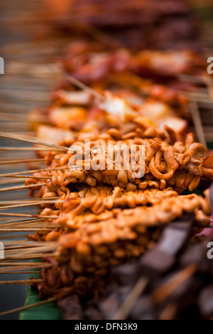 Chicken parts skewered onto sticks on a street food vendor's cart in Baclaran, Manila, Philippines. - Stock Image