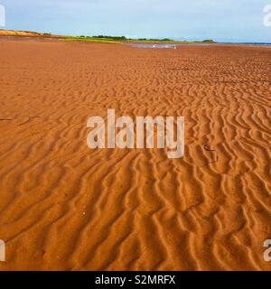 Red sand on beach in Prince Edward Island Canada - Stock Image