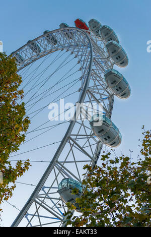 The iconic London Eye seen from below against a blue sky on a sunny day - Stock Image