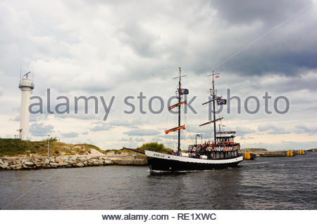 Kolobrzeg, Poland - August 10, 2018: Santa Maria Pirate excursion ship on the water with light house in the background on a cloudy day by the port - Stock Image