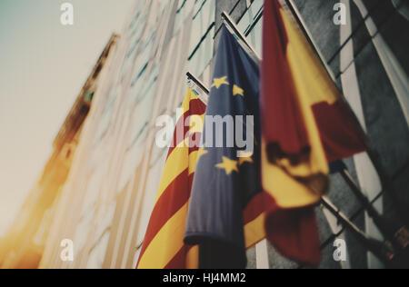 True tilt shift shooting of three waving flags on modern business office facade in Barcelona: European Union, Catalonia, - Stock Image