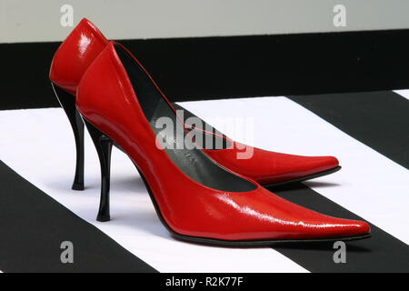 Red high heels on a black and twite striped floor - Stock Image