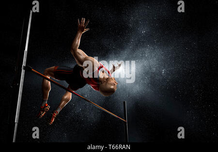 Male track and field athlete high jumping - Stock Image