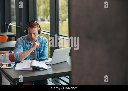 Shot of young male student preparing assignment in university library. Man with laptop reading book at college library. - Stock Image