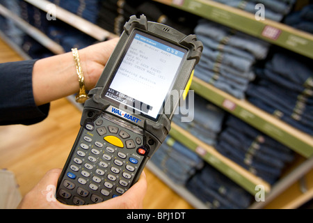 A sales associate uses a Telxon handheld scanner to read EPC/RFID labels on clothing at a Walmart Supercenter in - Stock Image