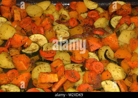 crispy grilled vegetarian and vegan oven vegetables seasoned with herbs and olive oil, ready to eat baked oven vegetables - Stock Image