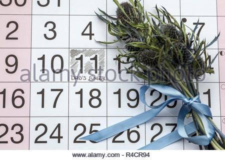 Dad's Funeral written on a calendar page with a posy of thistles - Stock Image
