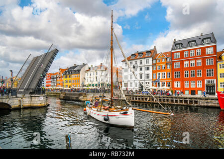 The Nyhavn bridge opens to let a small sailboat through the canal in the waterfront tourist area of Nyhavn in Copenhagen, Denmark. - Stock Image